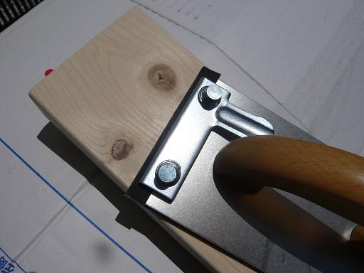 紙やすりをホルダーに付けて木の表面を仕上げる